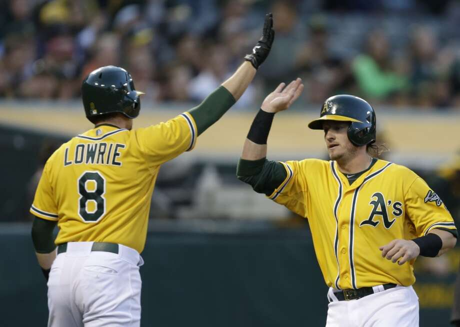 Jed Lowrie (8) congratulates Josh Donaldson after both scored on a single by Yoenis Cespedes. Photo: Ben Margot, Associated Press