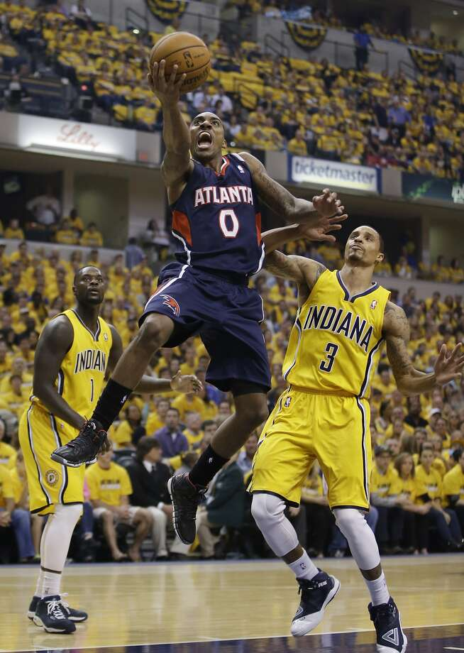 Atlanta Hawks' Jeff Teague zips past Indiana's Lance Stephenson (1) and George Hill on his way to 28 points. Photo: Darron Cummings, Associated Press