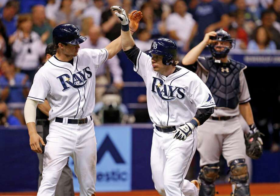 Tampa Bay Rays' Ryan Hanigan, center, is congratulated on his two-run home run by teammate Wil Myers in front of New York Yankees catcher Brian McCann during the fourth inning of a baseball game Saturday, April 19, 2014, in St. Petersburg, Fla. (AP Photo/Mike Carlson) ORG XMIT: FLMC109 Photo: Mike Carlson / FR155492 AP