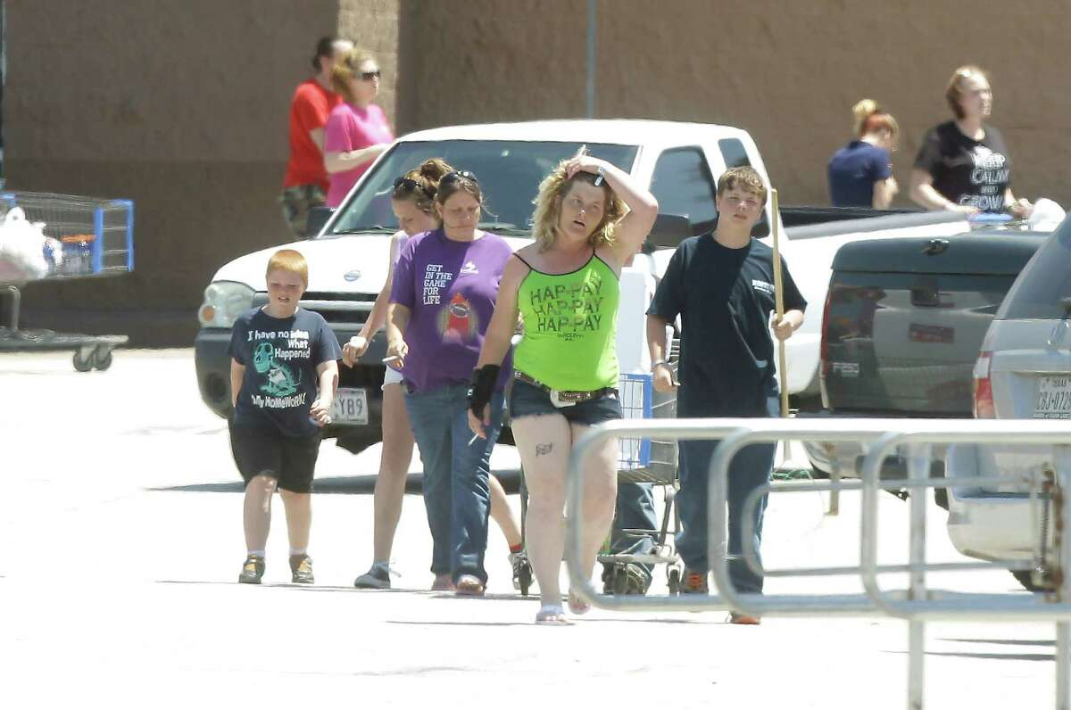 Customers leave the Wal-Mart shopping center after being kept inside for four hours while FBI bomb squad and Kemah police investigated a suspicious device in the parking lot on Saturday, April 19, 2014, in Kemah. ( J. Patric Schneider / For the Chronicle )
