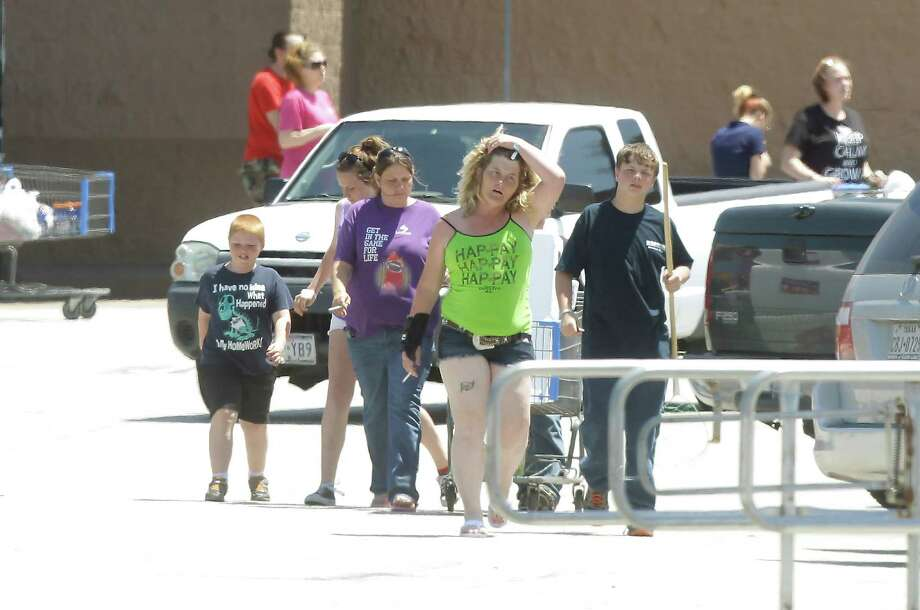 Customers leave the Wal-Mart shopping center after being kept inside for four hours while FBI bomb squad and Kemah police investigated a suspicious device in the parking lot on Saturday, April 19, 2014, in Kemah. ( J. Patric Schneider / For the Chronicle ) Photo: J. Patric Schneider, Freelance / © 2014 Houston Chronicle