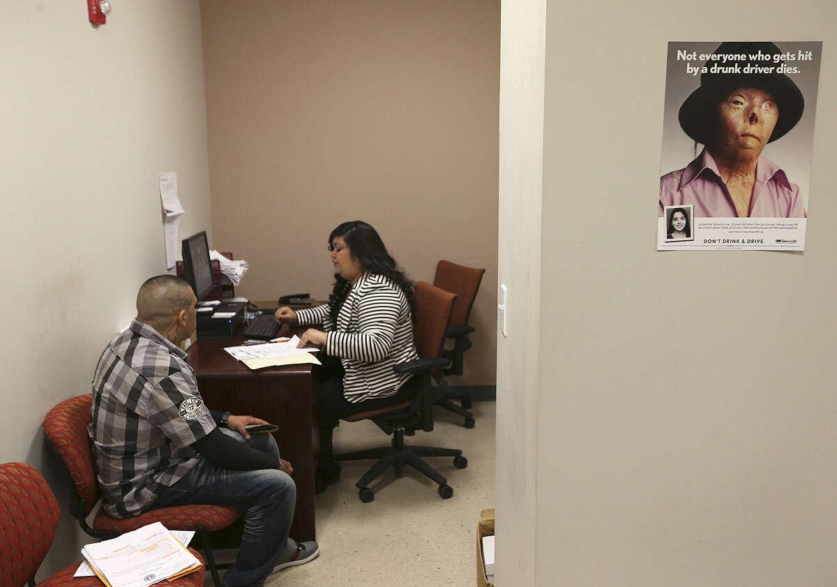 Pretrial bond officer Vanessa Espinoza processes a man during a DWI orientation at Bexar County Pretrial Services.