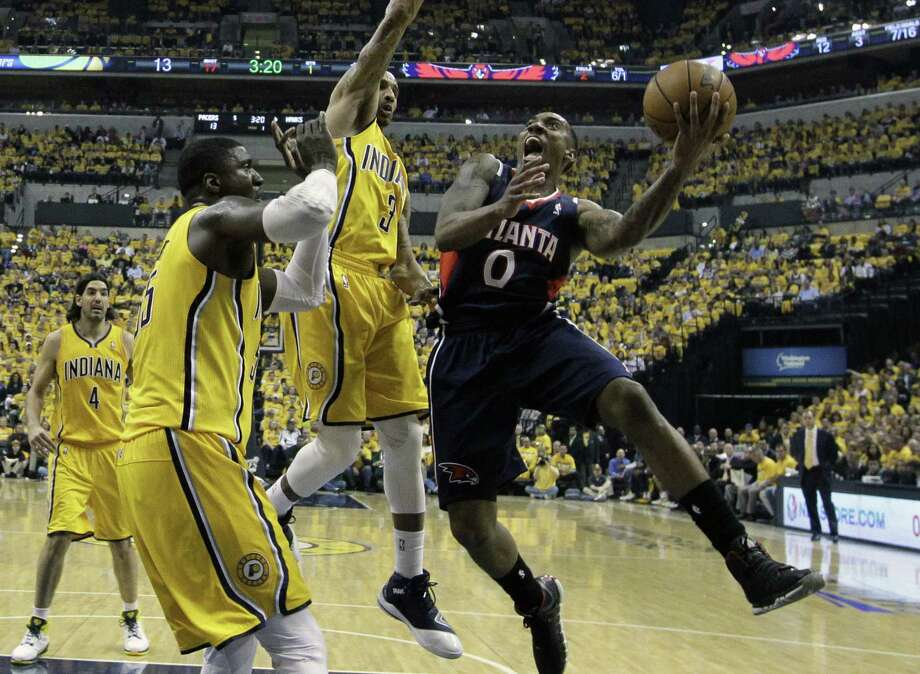 Atlanta's Jeff Teague, who had a playoff career-high 28 points, shoots against Indiana's Roy Hibbert (left) and George Hill. The Hawks won for the second time in Indianapolis this season. Photo: Darron Cummings / Associated Press / AP