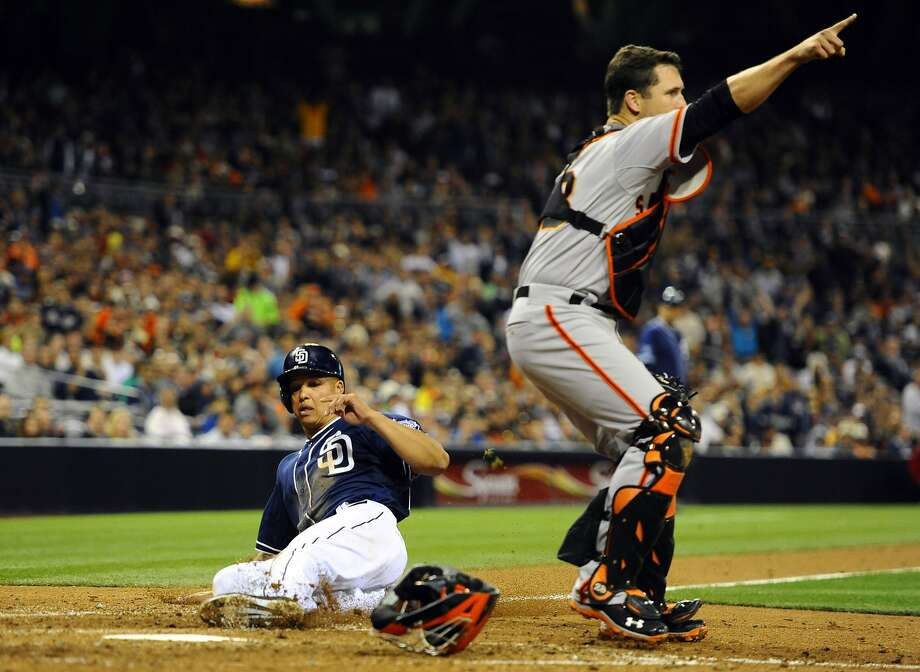 Will Venable slides home behind Giants catcher Buster Posey on a squeeze bunt by Chris Denorfia in the eighth inning to give the Padres a 3-1 lead. Photo: Christopher Hanewinckel, Reuters