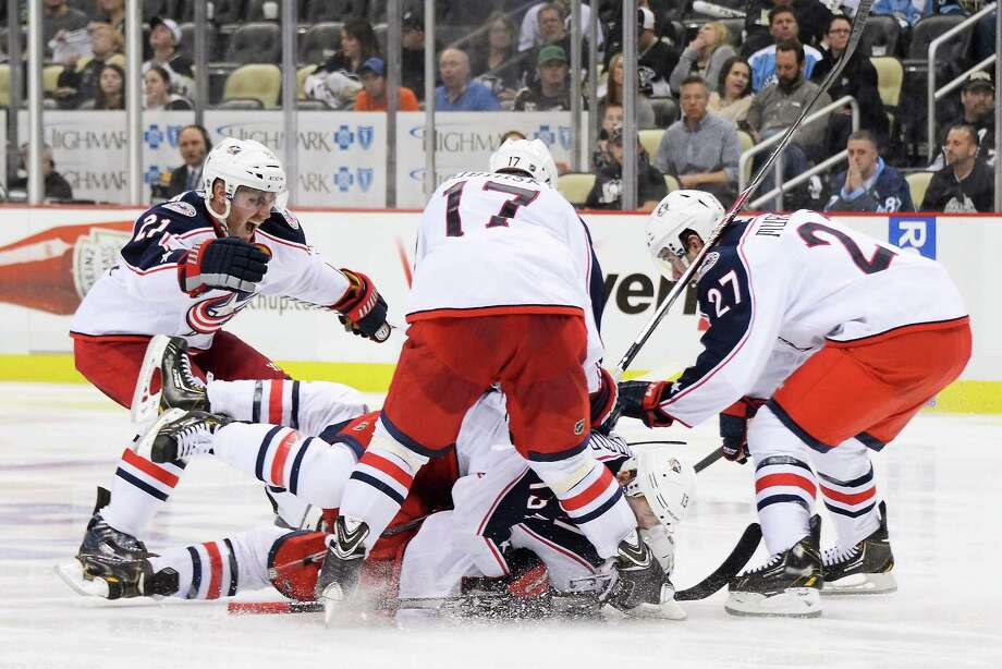 PITTSBURGH, PA - APRIL 19:  James Wisniewski #21, Brandon Dubinsky #17, Ryan Murray #27 and Cam Atkinson #13, all of the Columbus Blue Jackets, celebrate with Matt Calvert #11 who scored the game-winning goal in the second overtime against the Pittsburgh Penguins in Game Two of the First Round of the 2014 NHL Stanley Cup Playoffs on April 19, 2014 at CONSOL Energy Center in Pittsburgh, Pennsylvania. Columbus defeated Pittsburgh 4-3 for their franchise first playoff win.  (Photo by Jamie Sabau/NHLI via Getty Images) ORG XMIT: 485352575 Photo: Jamie Sabau / 2014 Getty Images