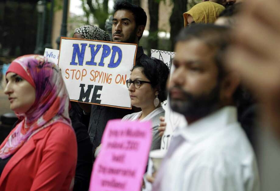 FILE - In this Aug. 28, 2014, file photo, a group of people hold signs protesting the New York Police Department's program of infiltrating and informing on Muslim communities during a rally near police headquarters in New York. On Tuesday, April 15, 2014, the NYPD confirmed it disbanded the special intelligence unit that monitored Muslim communities in New York and New Jersey. (AP Photo/Seth Wenig, File) ORG XMIT: NYR108 Photo: Seth Wenig / AP