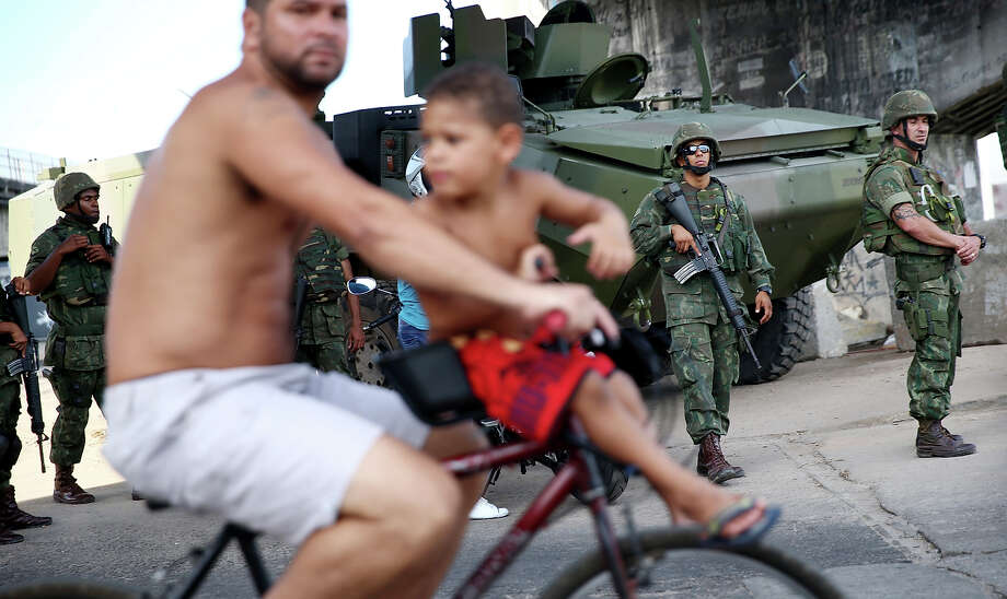 RIO DE JANEIRO, BRAZIL - APRIL 19:  Brazilian soldiers keep watch as a man and boy bike past in the occupied Complexo da Mare, one of the largest 'favela' complexes in Rio, on April 19, 2014 in Rio de Janeiro, Brazil. The Brazilian government has deployed nearly 3,000 federal troops to occupy the group of violence-plagued slums ahead of the June 12 start of the 2014 FIFA World Cup. The group of 16 communities house around 130,000 residents and had been dominated by drug gangs and militias. Mare is located close to Rio's international airport and has been mentioned as a likely pacification target for the police amid the city's efforts to improve security ahead of the 2014 FIFA World Cup and Rio 2016 Olympic Games.  (Photo by Mario Tama/Getty Images) *** BESTPIX *** Photo: Mario Tama / Getty Images / 2014 Getty Images