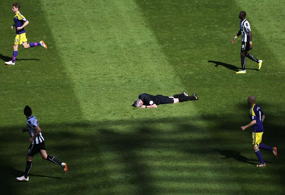 Referee Chris Foy, center, is laid on the pitch after being struck by a ball to the face during the English Premier League soccer match between Newcastle United and Swansea City at St James' Park, Newcastle, England, Saturday, April 19, 2014. (AP Photo/Scott Heppell) Photo: Scott Heppell, Associated Press