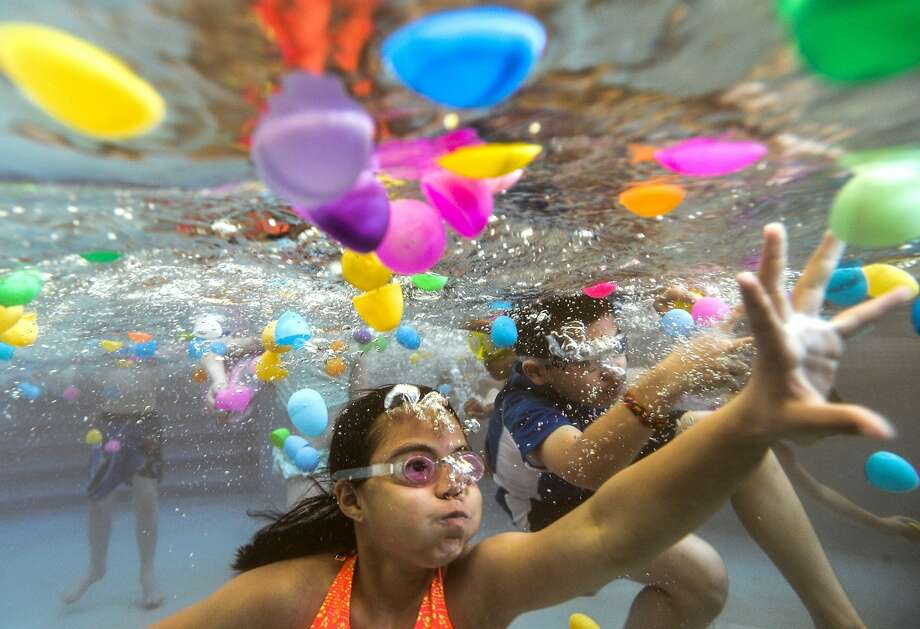 Ten-year olds Kaitlynn Tran of Chicago, and Michael Ramirez of Aurora, Ill., right, gather plastic eggs floating in the Peoria AquaPlex pool during an underwater egg hunt in Peoria, Ill. on Saturday, April 19, 2014. (AP Photo/Peoria Journal Star, Ron Johnson) Photo: Ron Johnson, Associated Press
