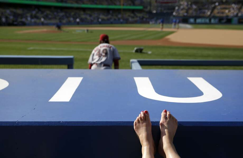 A fan rests her feet on the wall as Arizona Diamondbacks starting pitcher Mike Bolsinger walks out of the dugout before a baseball game against the Los Angeles Dodgers, Saturday, April 19, 2014, in Los Angeles. (AP Photo/Jae C. Hong) Photo: Jae C. Hong, Associated Press