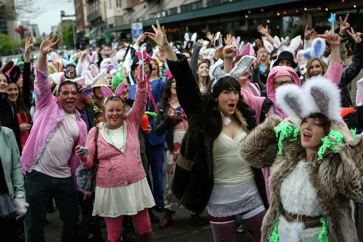 Participants march between bars during BunnyCon, a bunny-themed bar hop, on Saturday, April 19, 2014. Hundreds of floppy-eared people walked between downtown Seattle bars during the event.