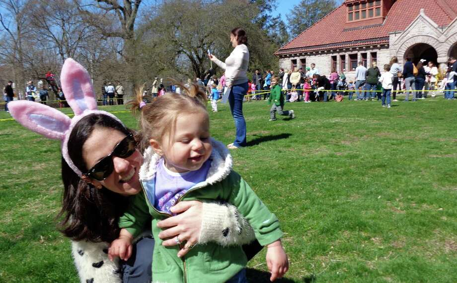 Sophia Granneberg, 1 1/2 years old, decided she didn't want to wear her bunny ears so her mother Chrissy Granneberg put them on instead at the Pequot Library's egg roll. Photo: Meg Barone / Fairfield Citizen
