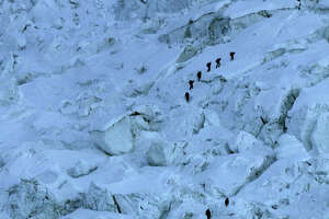FILE - In this Sunday, May 18, 2003 file photo, mountaineers pass through the treacherous Khumbu Icefall on their way to Mount Everest near Everest Base camp, Nepal. An avalanche swept down a climbing route on Mount Everest early Friday, killing at least 12 Nepalese guides and leaving three missing in the deadliest disaster on the world's highest peak.