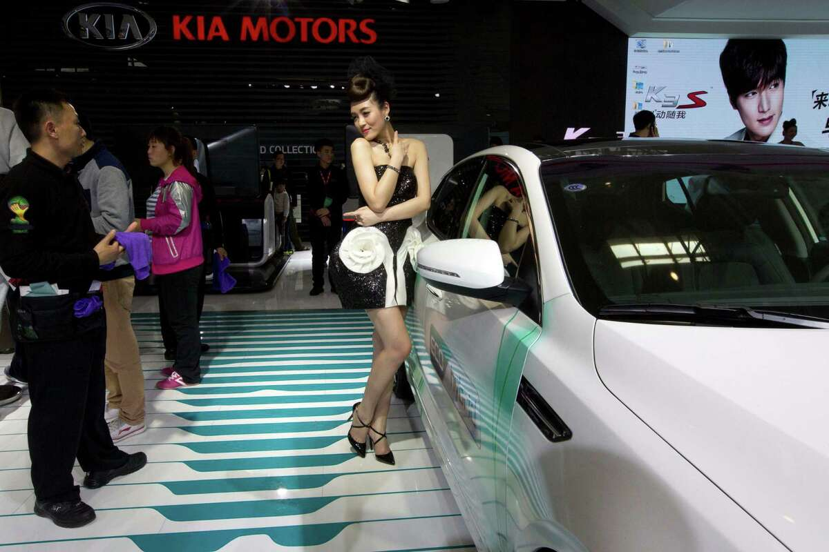 A car model poses next to a car from Kia Motors displayed at the China Auto show in Beijing, China, Sunday, April 20, 2014. Automakers are looking to China's biggest auto show this year to help boost sales in this huge but cooling market.