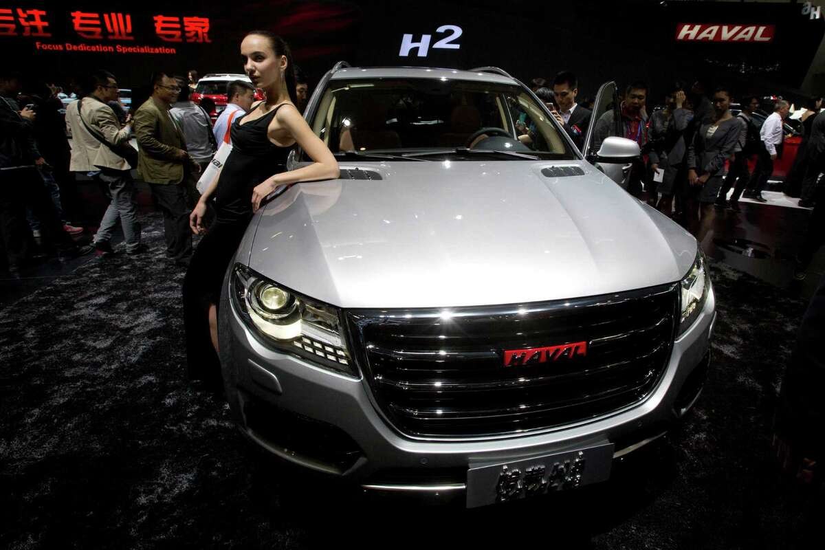 A model poses near Chinese SUV maker Great Wall Motors' Haval 8 displayed at the China Auto show held in Beijing, China, Sunday, April 20, 2014. Automakers are looking to China's biggest auto show this year to help boost sales in this huge but cooling market.