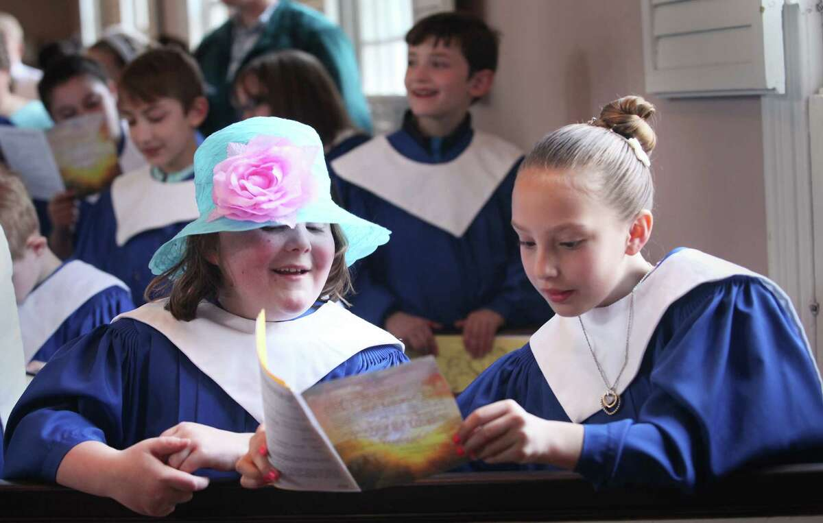 Amanda Sykes-Quirk, 7, left, and Madison Ritchie, 8, follow the Easter Service at the First United Church of Christ Congregational in Milford on Sunday, April 20, 2014.