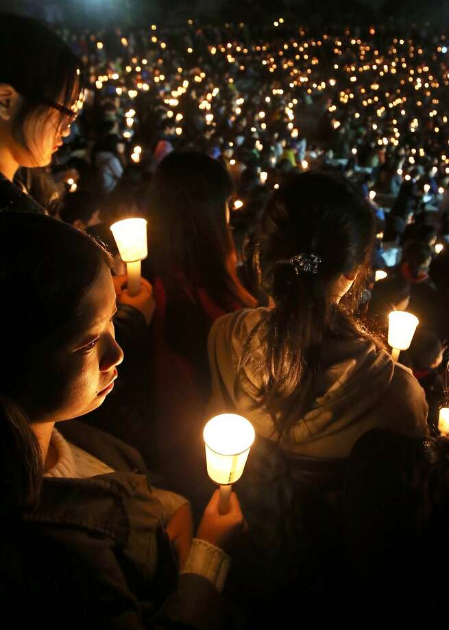 Danwon High school students and other South Koreans hold candles as they pray in Ansan for the safe return of missing ferry passengers. Photo: Handout, Getty Images
