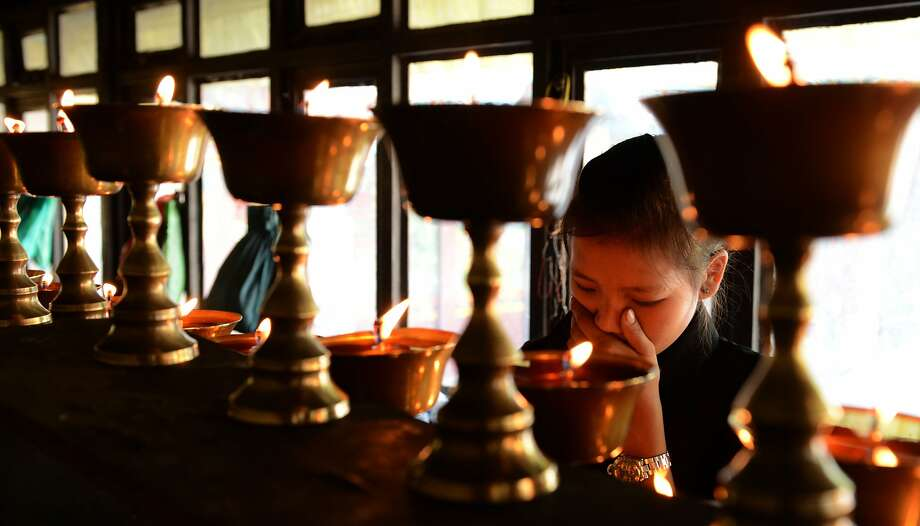 The daughter of avalanche victim Ang Kazi Sherpa lights lamps at Sherpa Monastery in Kathmandu. Photo: Prakash Mathema, AFP/Getty Images
