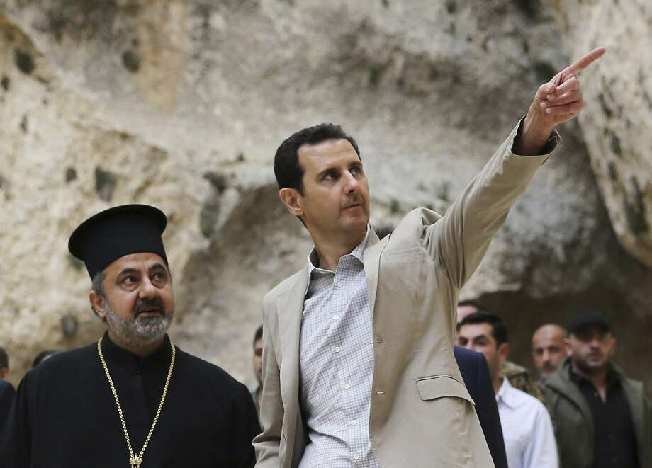 Syrian President Bashar al-Assad (R) visits Maaloula town, northeast of Damascus April 20, 2014, in this handout photograph released by Syria's national news agency SANA. Assad on Sunday visited Maaloula, an ancient Christian town recaptured from rebels last week, state media said, as he seeks to persuade minorities that the government is their best protection against hardline Islamists. Assad's Easter visit to Maaloula - a rare appearance outside central Damascus - also highlighted growing government confidence in recent gains against insurgents around the capital and along the Lebanese border. REUTERS/SANA/Handout via Reuters (SYRIA - Tags: POLITICS RELIGION CONFLICT CIVIL UNREST) ATTENTION EDITORS - THIS PICTURE WAS PROVIDED BY A THIRD PARTY. REUTERS IS UNABLE TO INDEPENDENTLY VERIFY THE AUTHENTICITY, CONTENT, LOCATION OR DATE OF THIS IMAGE. THIS PICTURE IS DISTRIBUTED EXACTLY AS RECEIVED BY REUTERS, AS A SERVICE TO CLIENTS. FOR EDITORIAL USE ONLY. NOT FOR SALE FOR MARKETING OR ADVERTISING CAMPAIGNS Photo: Sana, Reuters