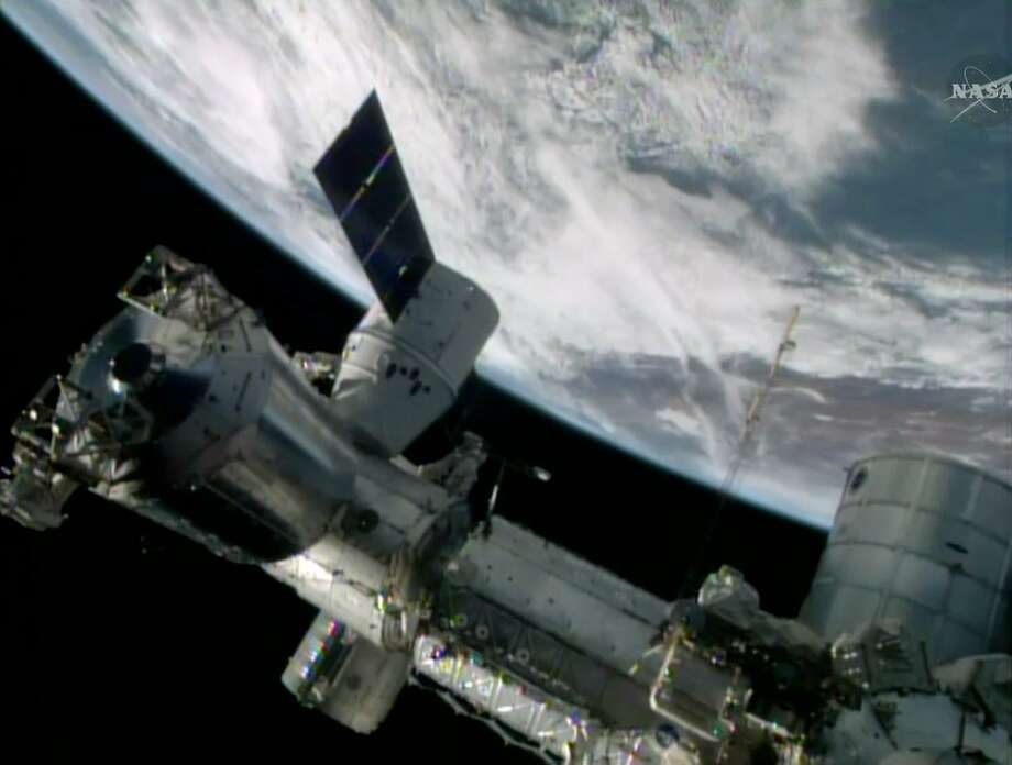 In this Sunday, April 20, 2014, image made from a frame grabbed from NASA-TV, the SpaceX Dragon resupply capsule begins the process of being berthed on to the International Space Station. At the time of this frame grab the capsule was traveling over the South America. (AP Photo/NASA-TV) Photo: Associated Press