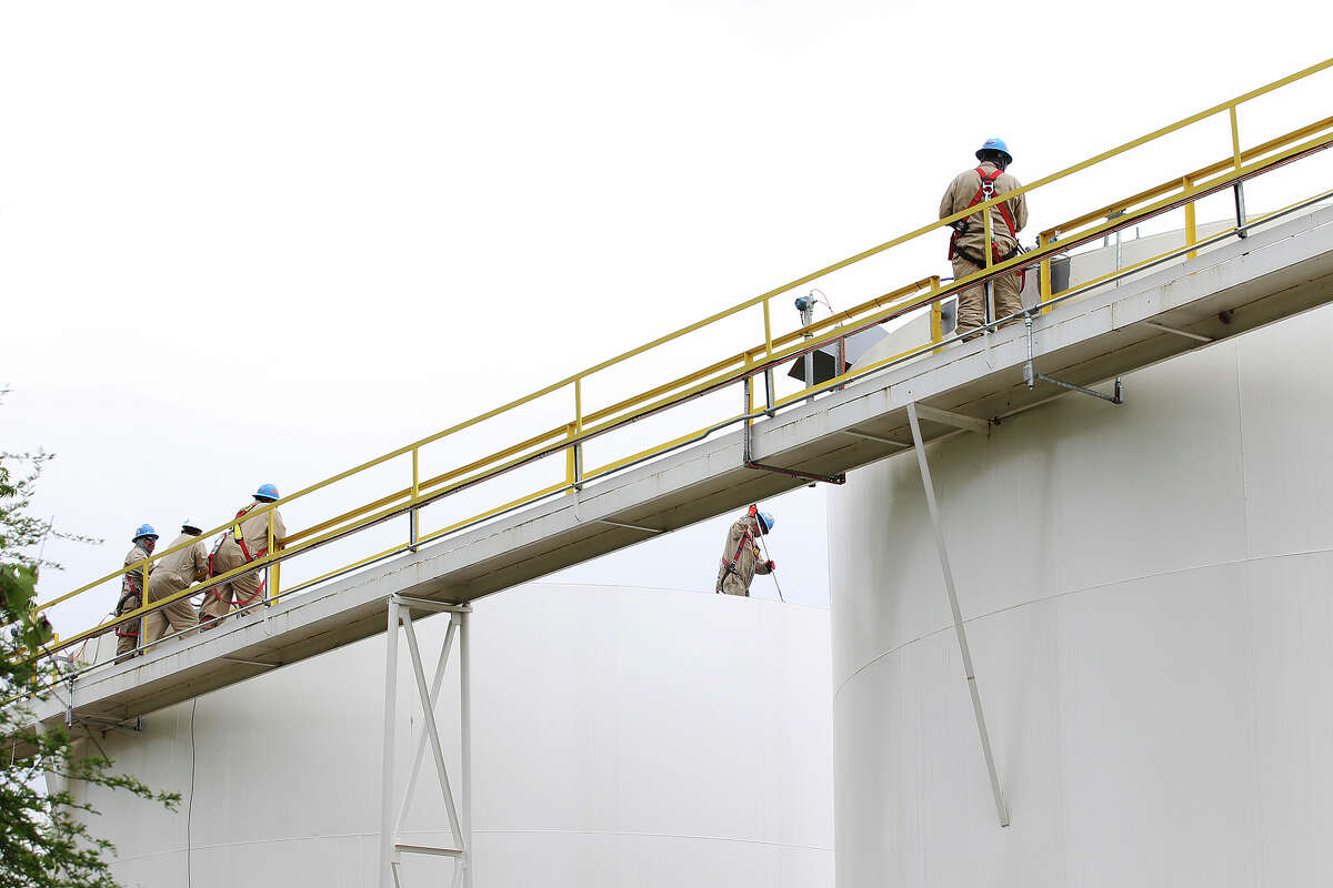 Workers are seen atop storage tanks at the Calumet Specialty Products Partners plant near the Mission Reach of the San Antonio River, Thursday, April 17, 2014.