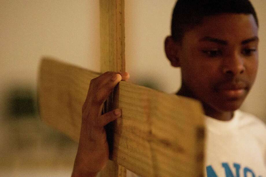 Jaden Ratcliff, 12, prepares to be tied to the cross in preparation for an Easter Sunday sermon at Providence Missionary Baptist Church, Sunday, April 20, 2014, in Houston. Photo: Cody Duty, Houston Chronicle / © 2014 Houston Chronicle