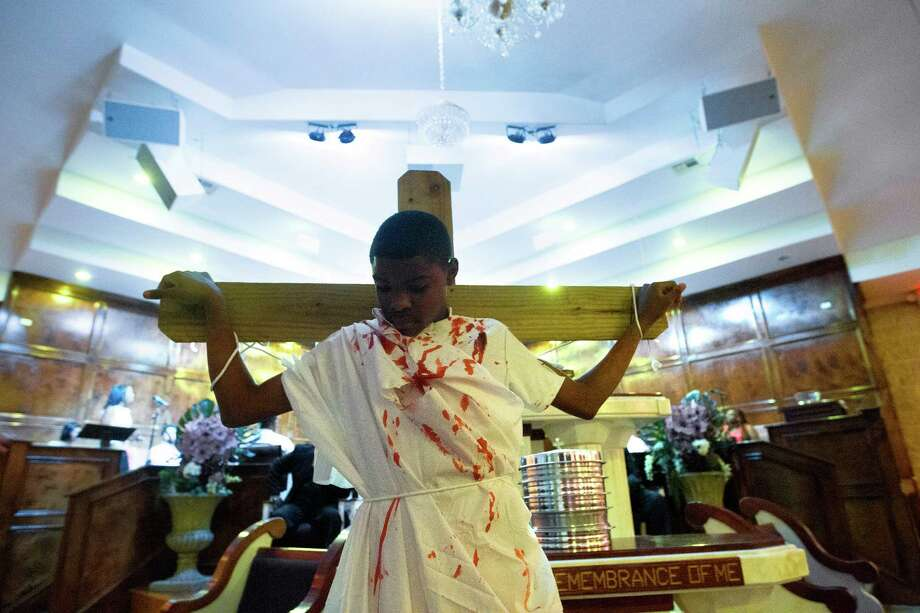 Jaden Ratcliff, 12, stands tied to a cross during an Easter Sunday sermon at Providence Missionary Baptist Church, Sunday, April 20, 2014, in Houston. Photo: Cody Duty, Houston Chronicle / © 2014 Houston Chronicle