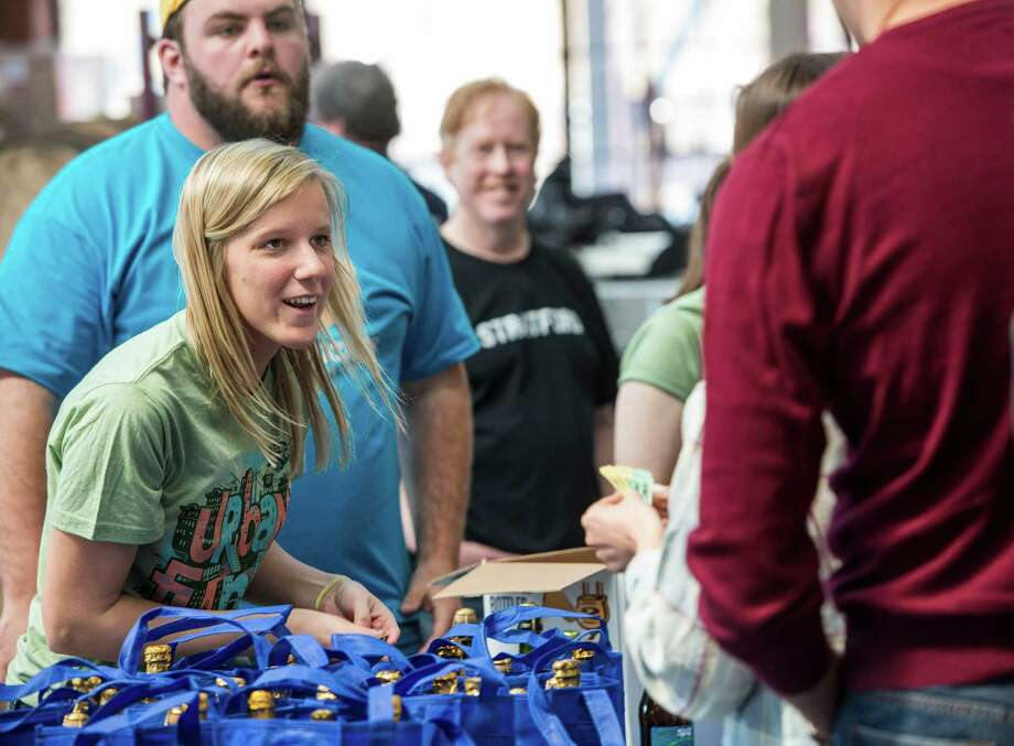 """Two Roads Brewing Company employee Kristen Malski handing out bags of limited edition beer to customers at the """"NorâÄôYeaster"""" limited edition beer release event at Two Roads Brewing Company, Stratford CT on Saturday, April, 19th, 2014. The brewery was releasing a limited supply of three different beers, Two Roads Krazy Pucker, HenryâÄôs Farm Double Bock Lager Aged in Rye Whiskey Barrels and Urban Funk Wild Ale. Photo: Mark Conrad / Connecticut Post Freelance"""
