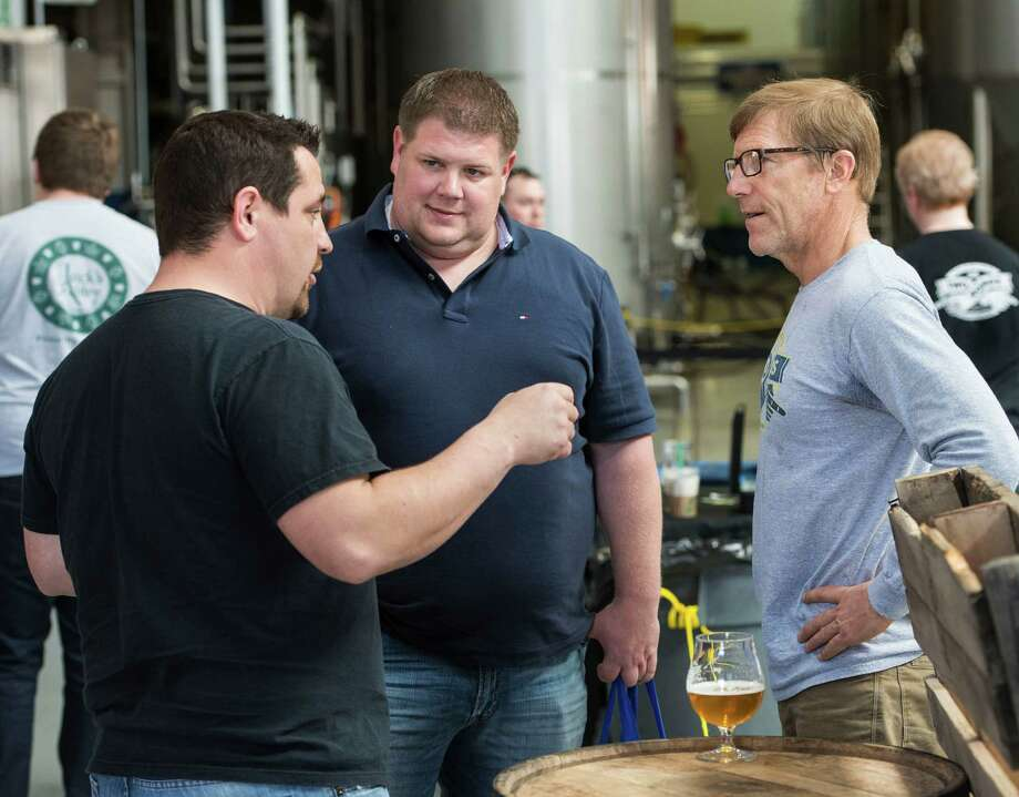 "Two Roads Brewing Company executive Brad Hittle (right) talks to a couple of customers at the ""NorâÄôYeaster"" limited edition beer release event at Two Roads Brewing Company, Stratford CT on Saturday, April, 19th, 2014. The brewery was releasing a limited supply of three different beers, Two Roads Krazy Pucker, HenryâÄôs Farm Double Bock Lager Aged in Rye Whiskey Barrels and Urban Funk Wild Ale. Photo: Mark Conrad / Connecticut Post Freelance"