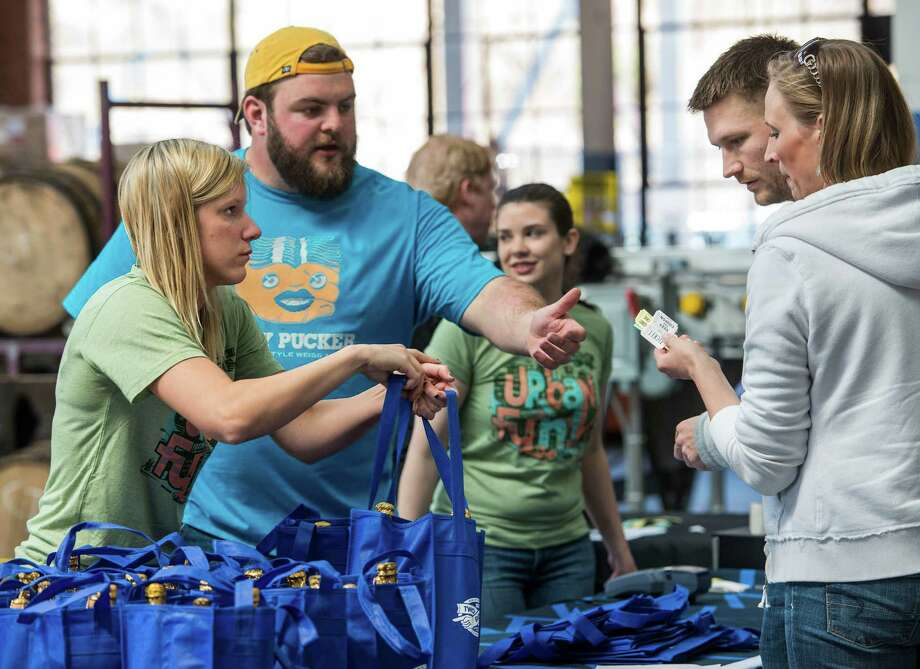 "Two Roads Brewing Company employees Kristen Malski, and Matt Green hand out bags of limited edition beer to customers at the ""NorâÄôYeaster"" limited edition beer release event at Two Roads Brewing Company, Stratford CT on Saturday, April, 19th, 2014. The brewery was releasing a limited supply of three different beers, Two Roads Krazy Pucker, HenryâÄôs Farm Double Bock Lager Aged in Rye Whiskey Barrels and Urban Funk Wild Ale. Photo: Mark Conrad / Connecticut Post Freelance"