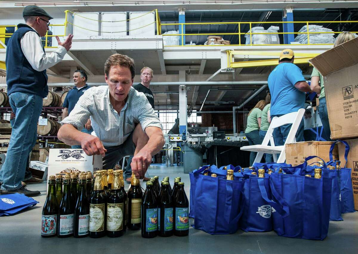 Two Roads Brewing Company executive Peter Doering unboxes bottles of beer to fulfill orders at the