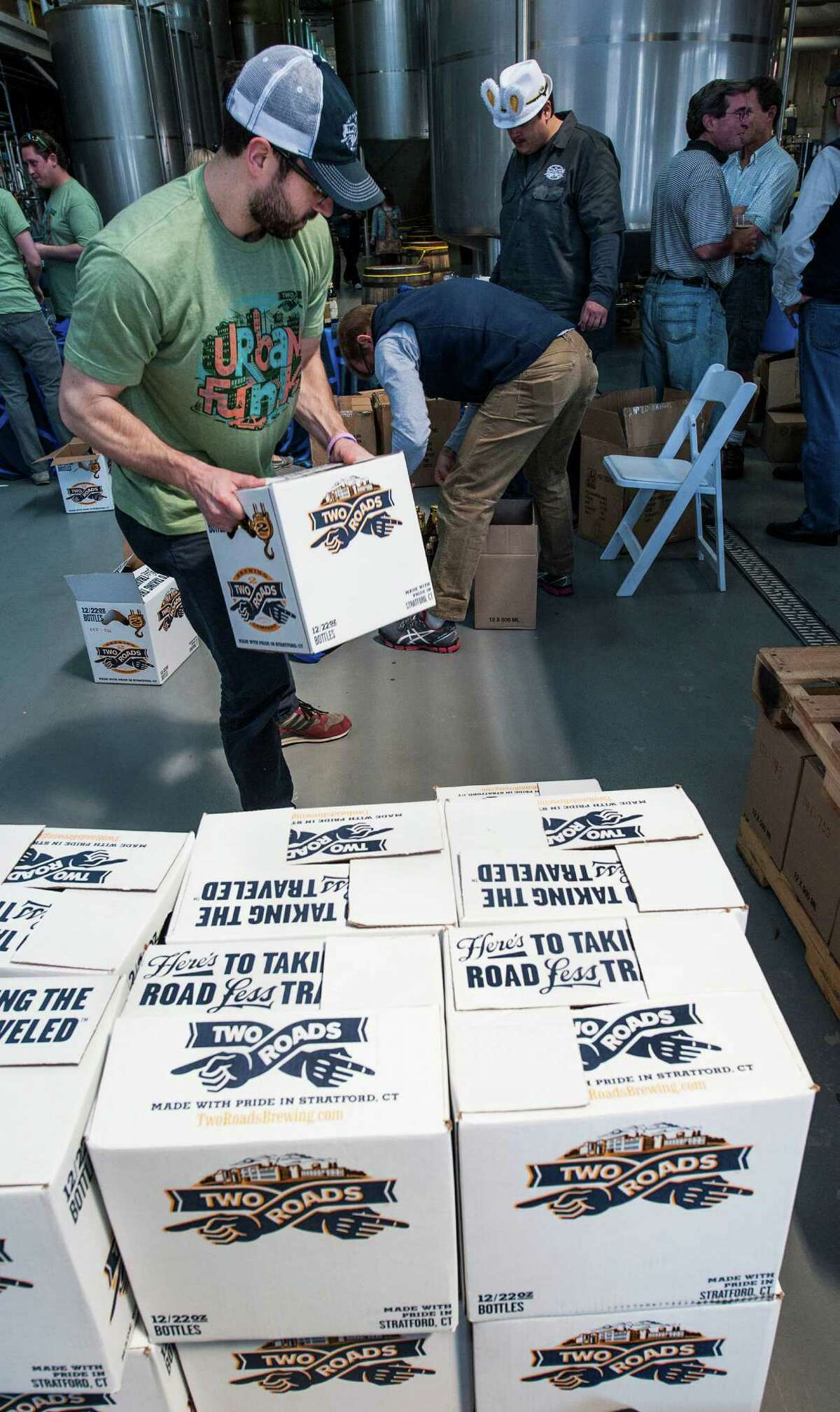 Two Roads Brewing Company employee Bill McAvoy carries boxes of beer to fulfill orders at the
