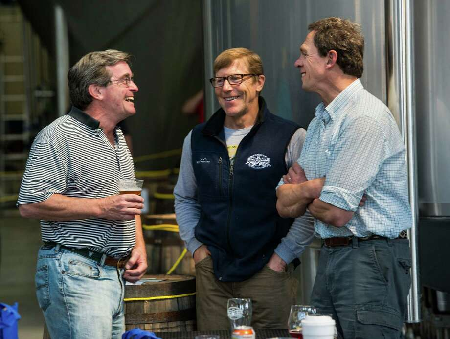"""Two Roads Brewing Company executives Brad Hittle and Peter Doering (center and right) talk to George Wyper (left) at the """"NorâÄôYeaster"""" limited edition beer release event at Two Roads Brewing Company, Stratford CT on Saturday, April, 19th, 2014. The brewery was releasing a limited supply of three different beers, Two Roads Krazy Pucker, HenryâÄôs Farm Double Bock Lager Aged in Rye Whiskey Barrels and Urban Funk Wild Ale. Photo: Mark Conrad / Connecticut Post Freelance"""