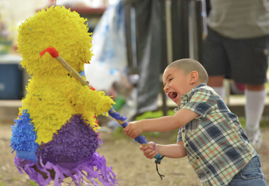 Devin Sanchez stikes the pinata with all his might during a family get-together in Brackenridge Park Sunday. Photo: Robin Jerstad