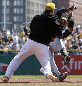Pittsburgh Pirates' Travis Snider, left, takes down Milwaukee Brewers' Carlos Gomez during a skirmish between the teams during the third inning of a baseball game in Pittsburgh, Sunday, April 20, 2014. Gomez and Snider were ejected from the game. (AP Photo/Gene J. Puskar)