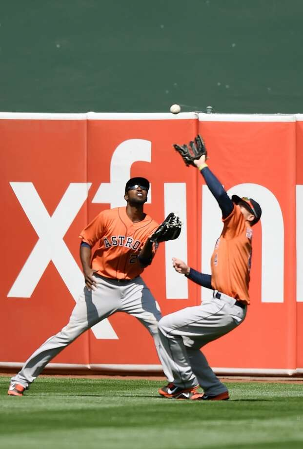 George Springer, right, catches this fly ball off the bat of Alberto Callaspo, while avoiding a collision with center fielder Dexter Fowler in the bottom of the sixth inning. Photo: Thearon W. Henderson, Getty Images
