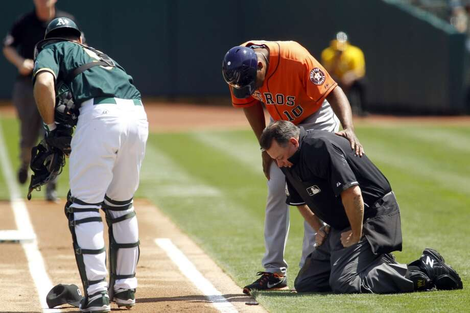 Homeplate umpire Andy Flecther is tended to by Astros first base coach Tarrik Brock after taking a spill. Photo: Matthew Sumner, Associated Press