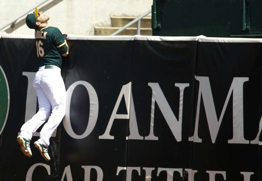 Josh Reddick climbs the wall chasing after Marwin Gonzalez's solo homer in the fourth inning. Photo: Matthew Sumner, Associated Press