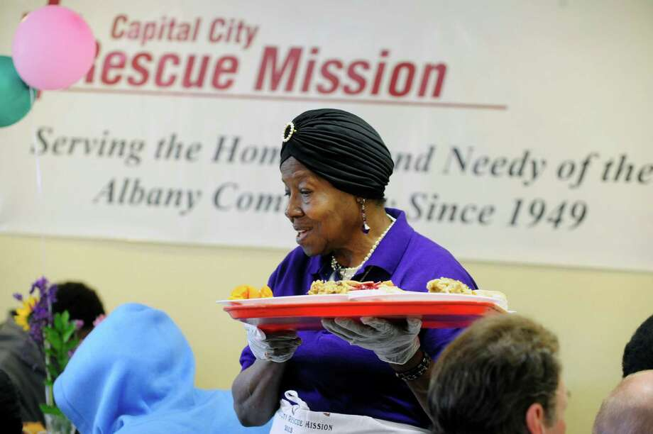 Hettie Dorsey, a volunteer with Trinity Church in Watervliet, serves plates of food to guests at the Easter dinner at the Capital City Rescue Mission on Sunday, April 20, 2014, in Albany, N.Y.  The mission held a service before the dinner.     Dorsey said that she volunteers at many of the holidays at the mission and that a group of people from Trinity Church volunteer at the mission about twice a month.  (Paul Buckowski / Times Union) Photo: Paul Buckowski / 00026548A