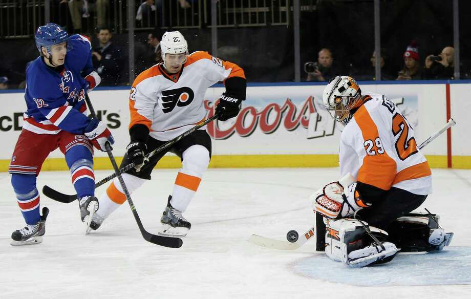Philadelphia Flyers goalie Ray Emery (29) blocks a shot by New York Rangers right wing Jesper Fast (12), of Sweden, with Flyers defenseman Luke Schenn (22) defending, in the second period of Game 2 of the first round of the Stanley Cup hockey playoffs at Madison Square Garden in New York , Sunday, April 20, 2014.  (AP Photo/Kathy Willens) ORG XMIT: MSG104 Photo: Kathy Willens / AP
