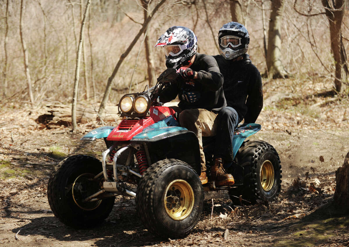 A pair of teens race their quad motorcycle on the trails at Eisenhower Park in Milford, Conn. on Sunday, April 20, 2014.
