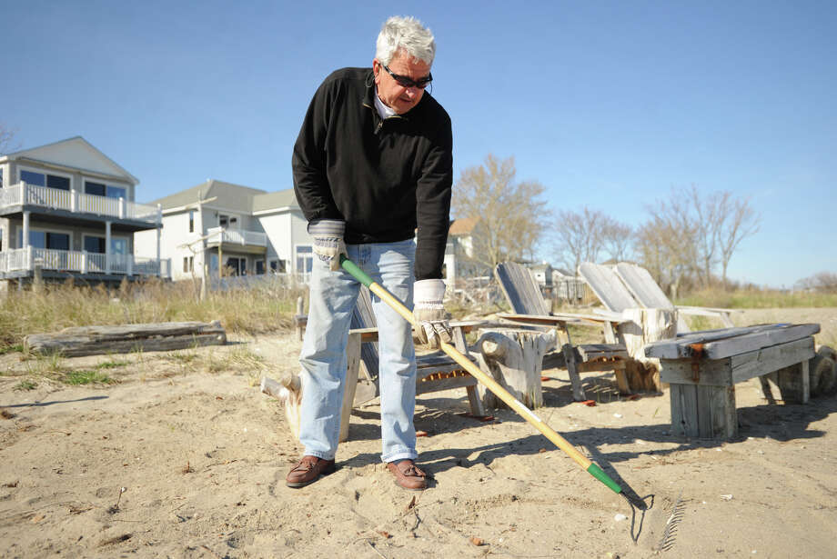 George Dewey, of Milford, rakes clean the sitting area outside his beachfront home on Smith's Point Road in Milford, Conn. on Sunday, April 20, 2014. Photo: Brian A. Pounds / Connecticut Post