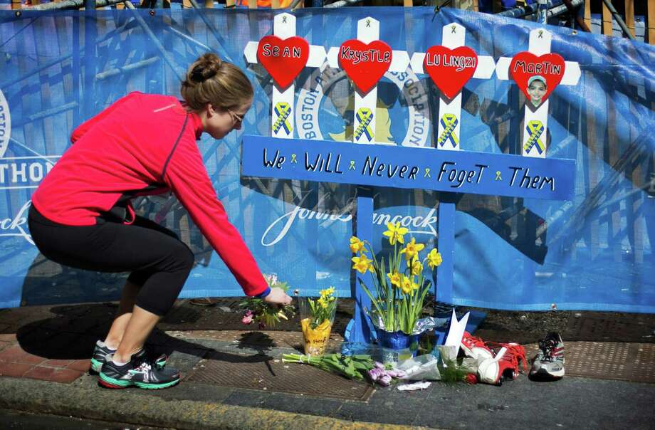 Boston Marathon runner Jessica Boucher, of Arlington, Va., places flowers at a memorial honoring the victims of the 2013 Boston Marathon bombings, Sunday, April 20, 2014, in Boston. The memorial is where the first explosion happened last year near the finish line. (AP Photo/Robert F. Bukaty) ORG XMIT: MARB101 Photo: Robert F. Bukaty / AP
