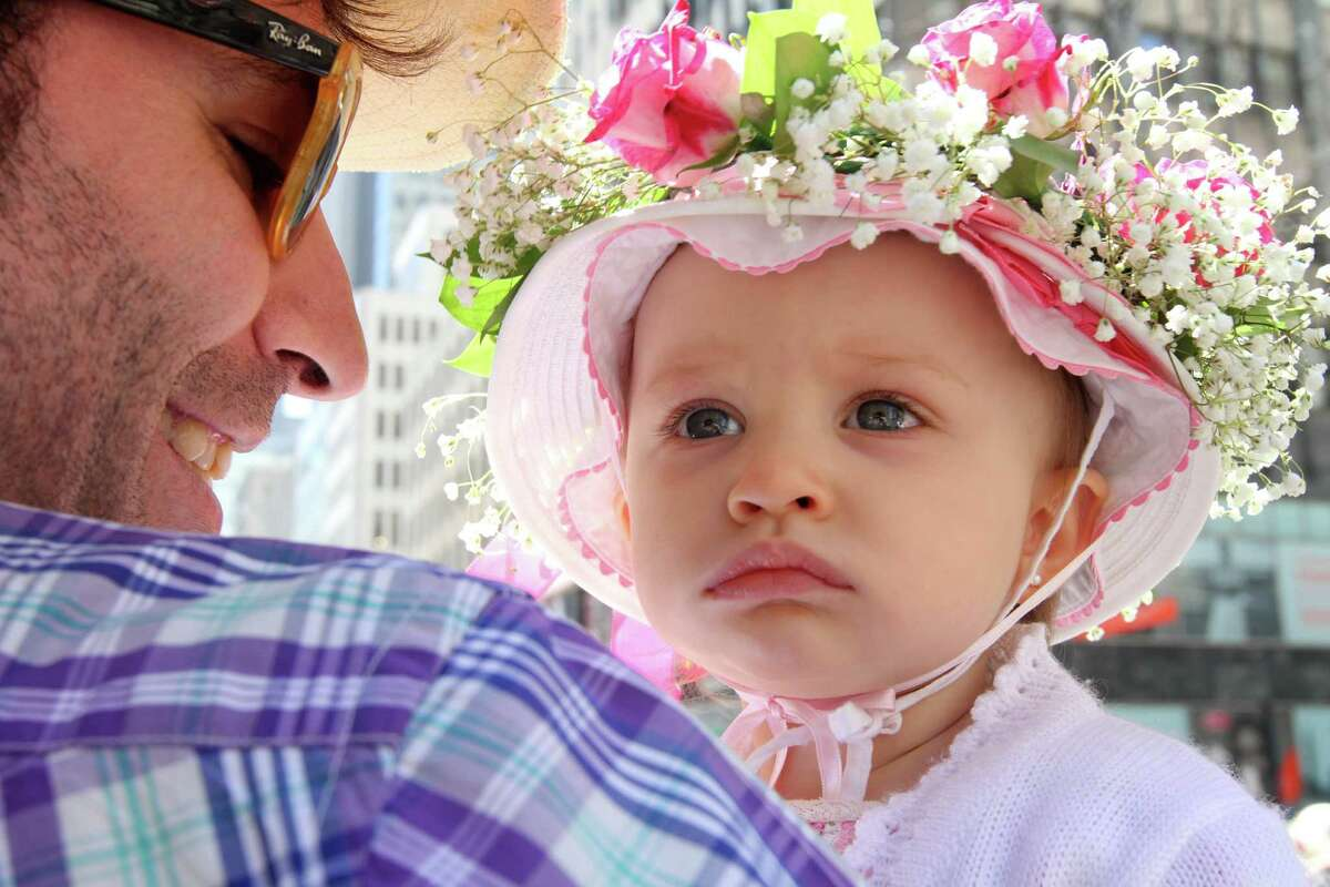 Secho Rodriguez, left, holds his 14 month old daughter Caetana Boente Rodriguez as they make their way along New York's Fifth Avenue during the Easter Parade, Sunday, April 20, 2014. (AP Photo/Tina Fineberg) ORG XMIT: NYTF103