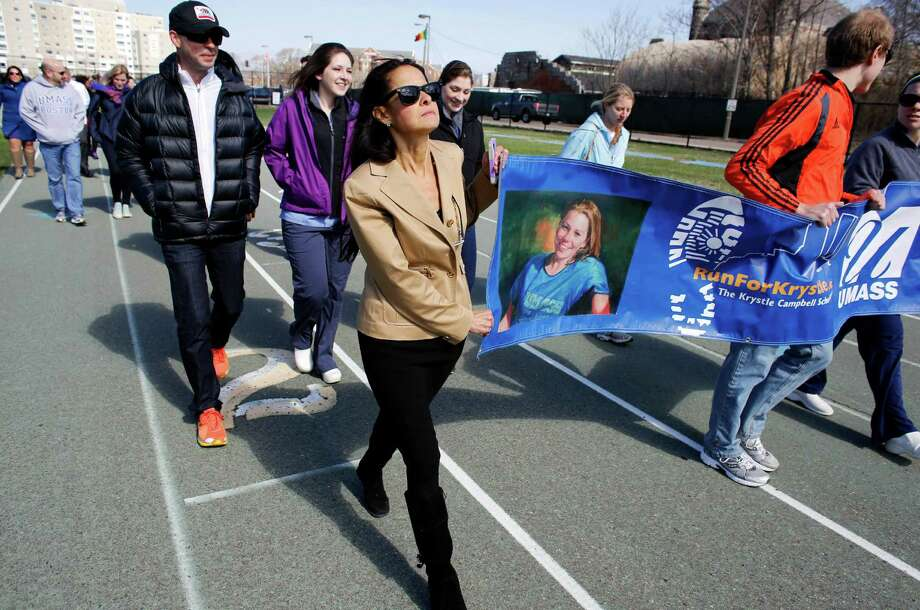 ADVANCE FOR MONDAY, APRIL 21, 2014 - In this Thursday, April 17, 2014, photo, University of Massachusetts nursing professor Adrienne Wald, center, helps carry a banner that features a photo of Krystle Campbell, a UMass nursing student who died in the Boston Marathon bombings in 2013, during a tribute walk on a track at the school in Boston. Wald, who has run the Boston Marathon five time, organized a group of her students last year to work as race volunteers on the sweep team, standing with wheelchair runners they expected to be dehydrated or otherwise needing minor medial care. None of her students was injured in the bombing. (AP Photo/Steven Senne) ORG XMIT: MASR103 Photo: Steven Senne / AP