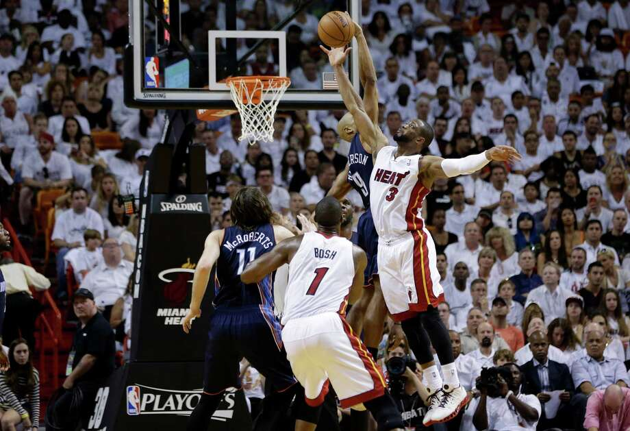 Miami Heat's Dwyane Wade (3) shoots over Charlotte Bobcats' Gerald Henderson, second from right, during the second half in Game 1 of an opening-round NBA basketball playoff series on Sunday, April 20, 2014, in Miami. The Heat defeated the Bobcats 99-88. (AP Photo/Lynne Sladky) ORG XMIT: AAA117 Photo: Lynne Sladky / AP