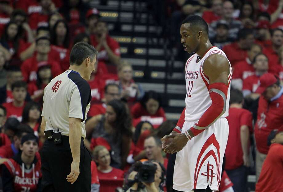 Rockets center Dwight Howard  right, discusses a call with NBA official Scott Foster. Photo: James Nielsen, Houston Chronicle