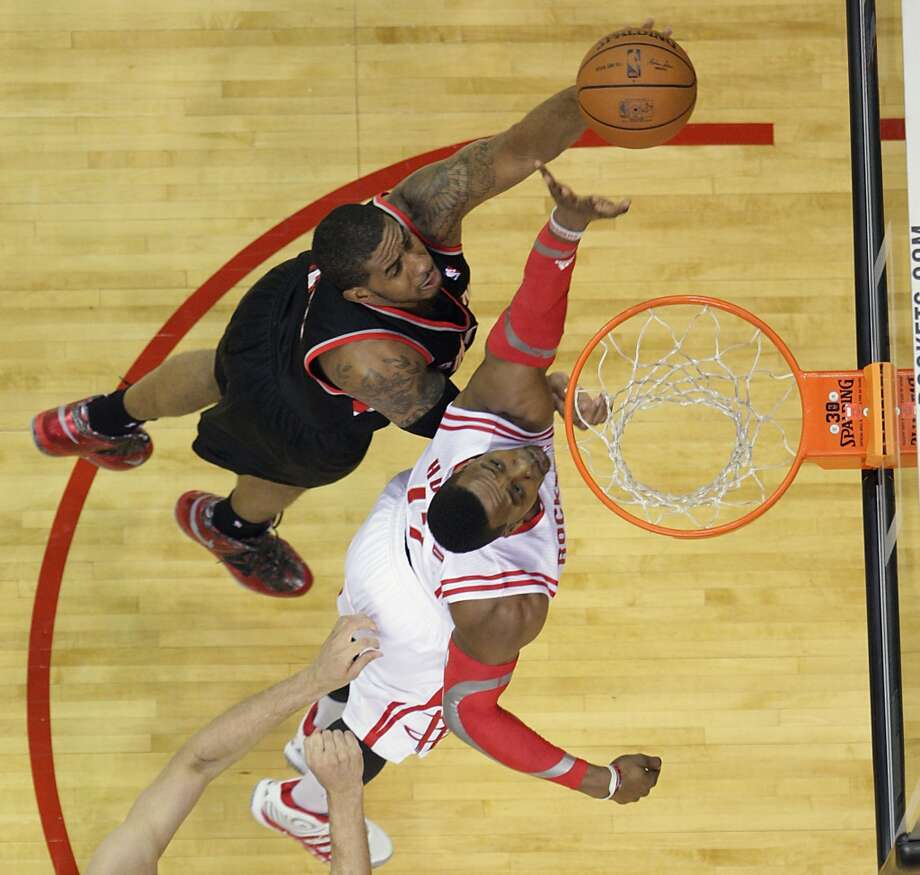 Dwight Howard bottom, blocks a shot by LaMarcus Aldridge. Photo: James Nielsen, Houston Chronicle