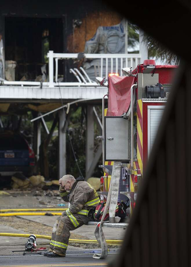 A Murrells Inlet-Garden City Fire Department firefighter sits outside the scene of a house fire Sunday, April 20, 2014, in Garden City Beach, S.C. Horry County chief deputy coroner Tamara Willard  one person is dead and several others needed hospital treatment after a blaze at a three-story house in Garden City Beach. (AP Photo/The Sun News, Randall Hill) Photo: Randall Hill, Associated Press