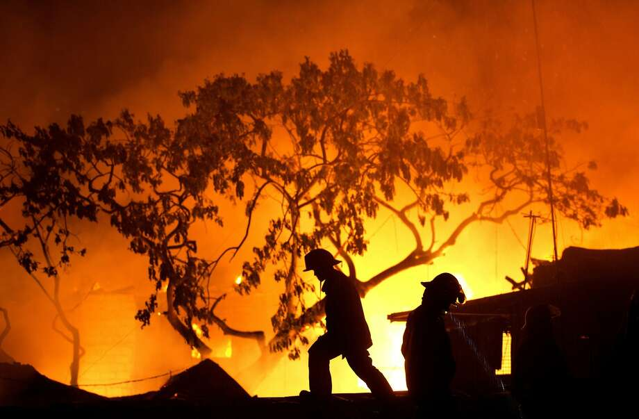 Filipino firefighters walk on the roof of a house as a huge fire rages through a slum area in Manila on April 20, 2014. Almost 1,000 families were affected by the fire according to local media reports. AFP PHOTO/NOEL CELISNOEL CELIS/AFP/Getty Images Photo: Noel Celis, AFP/Getty Images